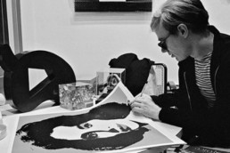 Andy Warhol signing a print, 1965.