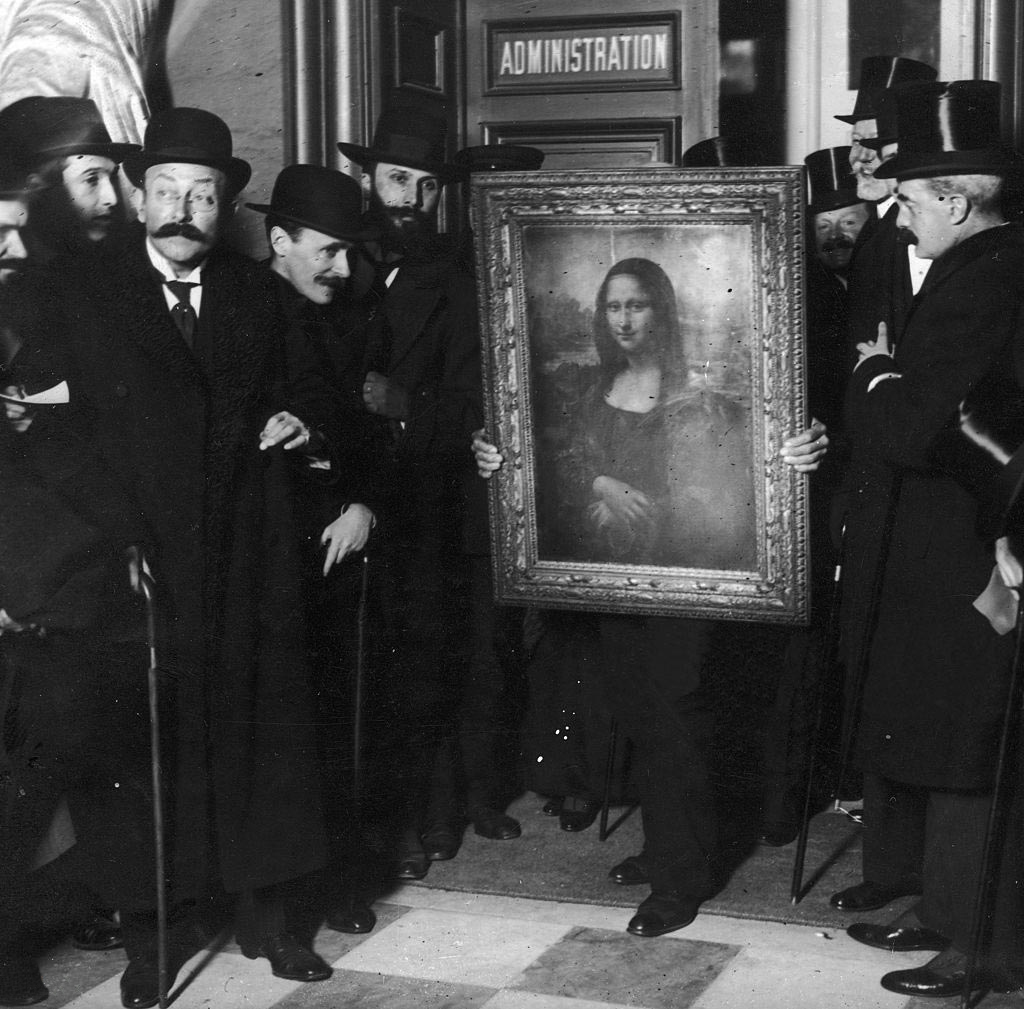 Officials gather around Leonardo da Vinci's 'Mona Lisa' upon its return to Paris, 1914.