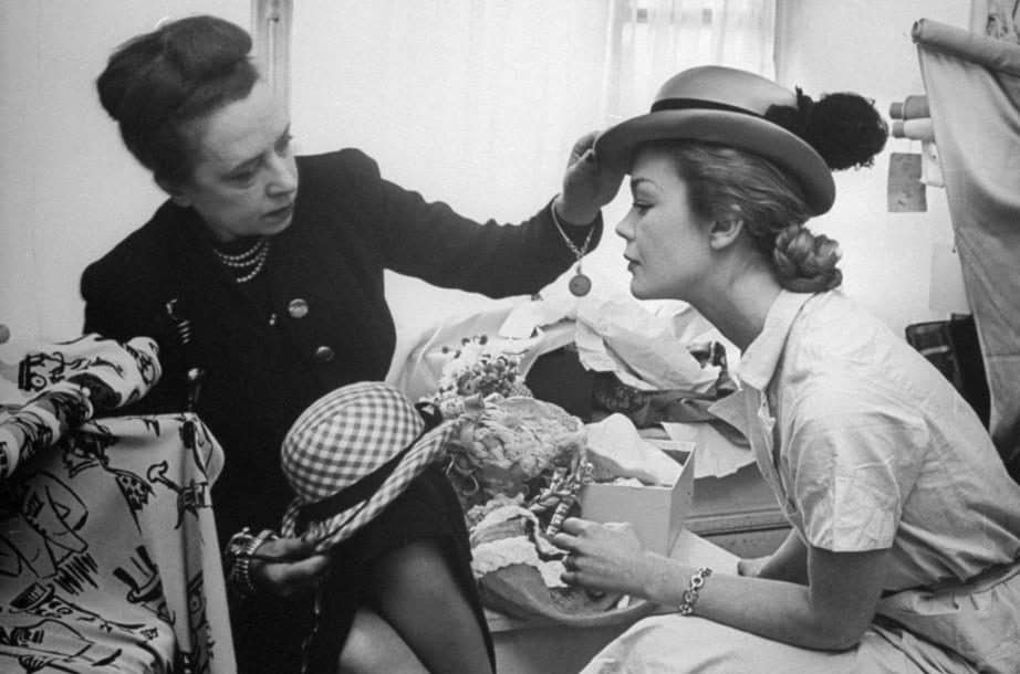 Elsa Schiaparelli trying out hats in her studio (1951)