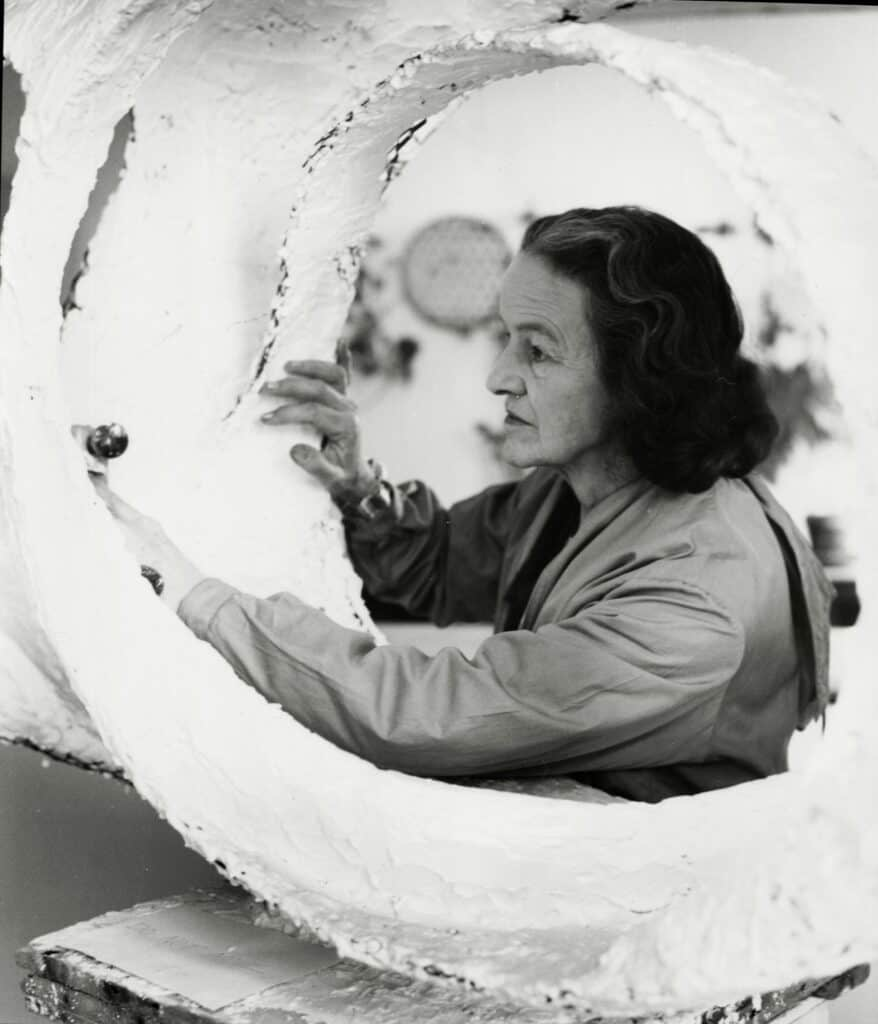 Hepworth at work on the plaster prototype for Oval Form (Trezio) in her Palais de Danse studio, St Ives, 1963. Photograph by Val Wilmer. Courtesy Bowness. Barbara Hepworth © Bowness.