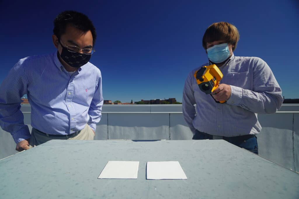 Purdue researchers Xiulin Ruan and Joseph Peoples use an infrared camera to compare the cooling performance of white paint samples on a rooftop. Credit: Purdue University photo/Jared Pike. Whitest white