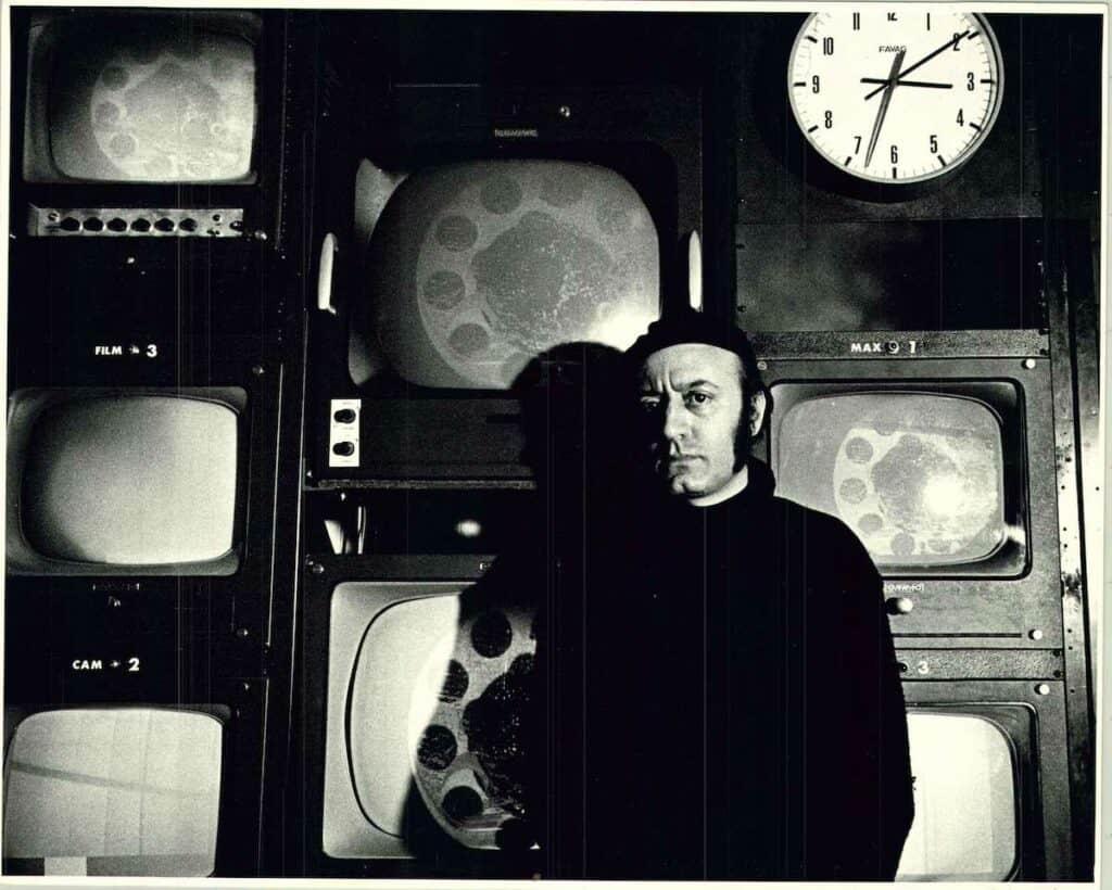 Aldo Tambellini in front of televisions. Courtesy of The Aldo Tambellini Art Foundation.