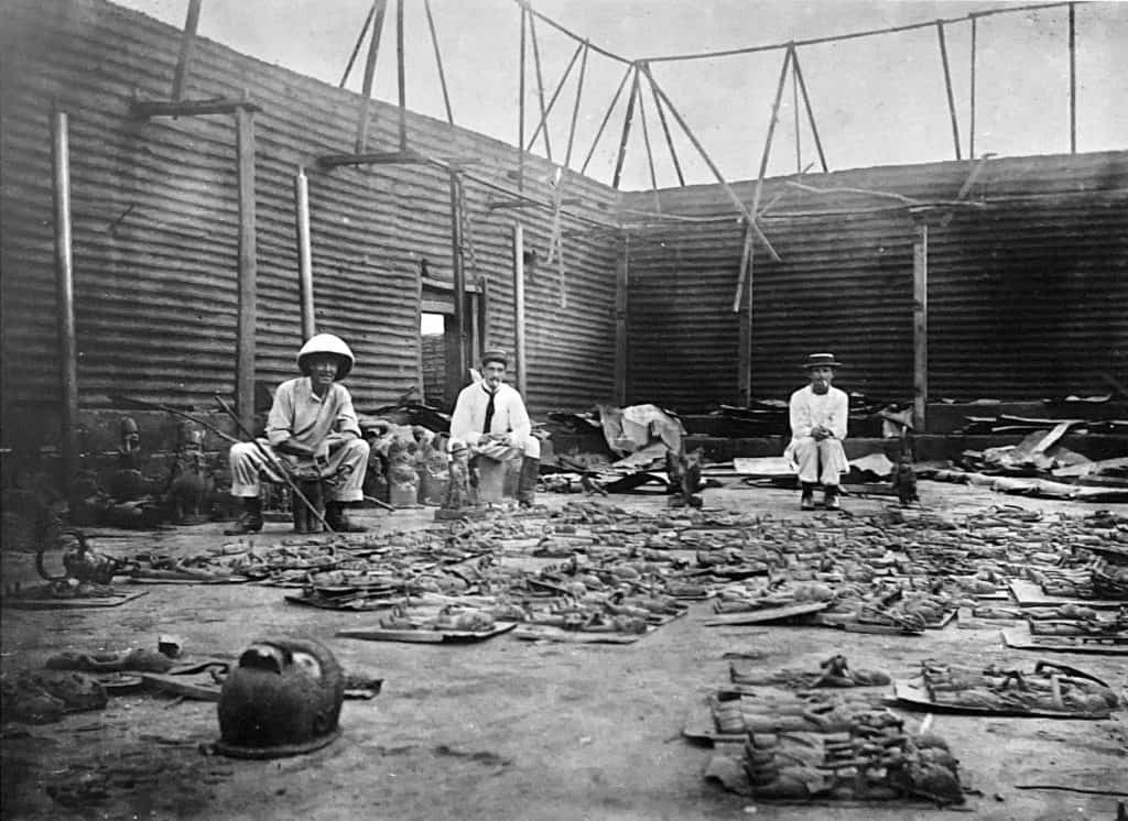 Interior of the Royal Palace during looting, showing Captain Charles. Herbert Philip Carter, 'E.P. Hill,' and an unnamed man in February 1897. Pitt Rivers Museum (accession number 1998.208.15.11).